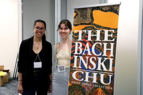 Nakita Byrne-Mamahit and Anna Sutton standing next to a sign for the U of G's Bachinski/Chu Print Study Collection