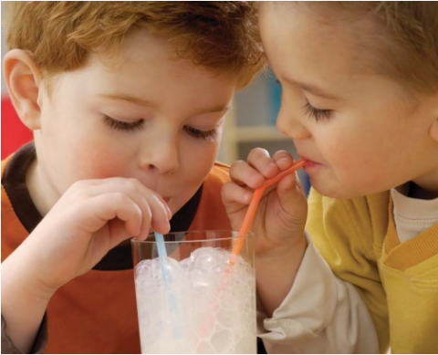 two kids sharing a glass of milk