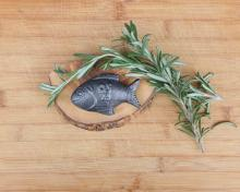 The lucky iron fish on a cutting board with rosemary around it
