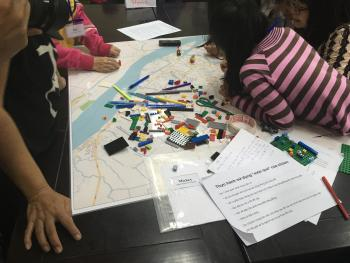 Girls surrounding a map with lego and documents