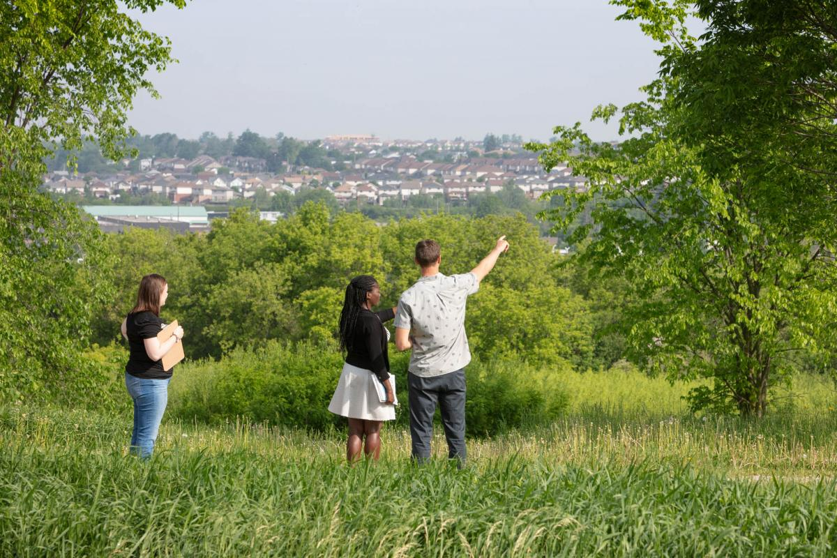 Three people standing in open field looking at subdivision of houses