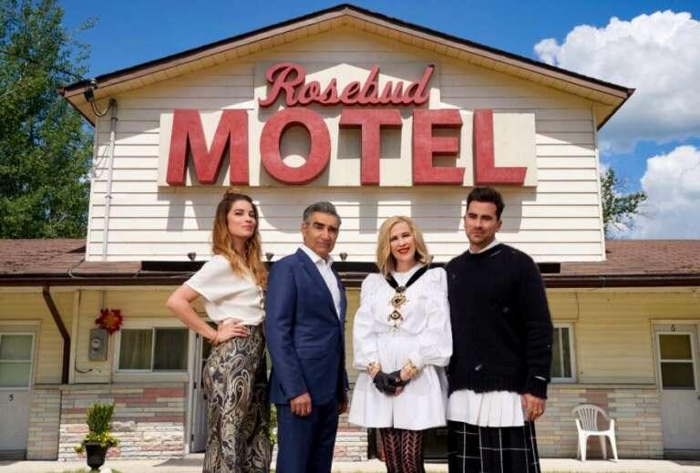 Four people standing outside in front of motel