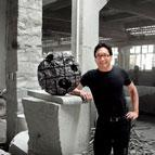 Colin Okashimo standing next to sculpture