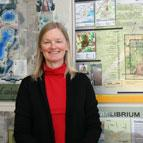 Karen Landman standing against posters