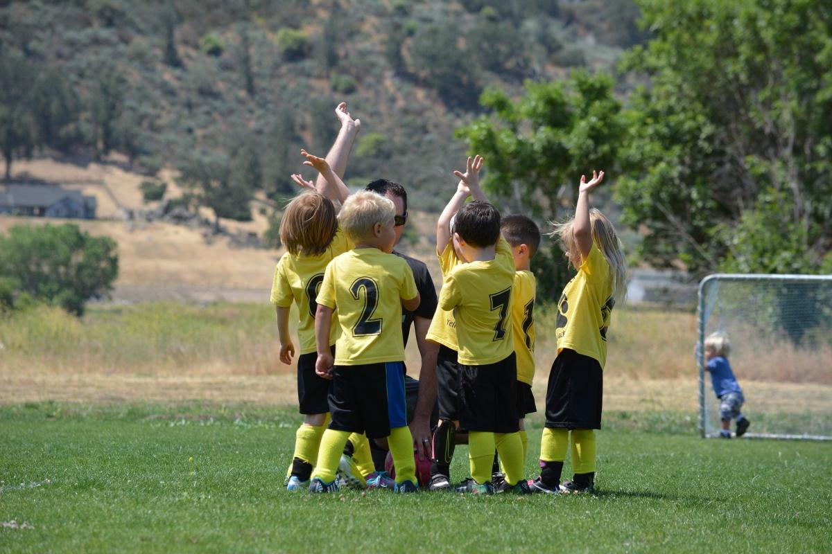 Children's soccer team together listening to coach