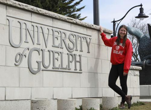 Student in front of University of Guelph stone wall