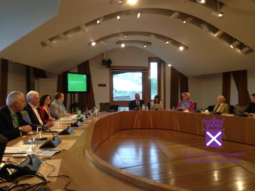 People sitting around oval table presenting to the Scottish Parliamentary Cross Party Committee on Rural Policy
