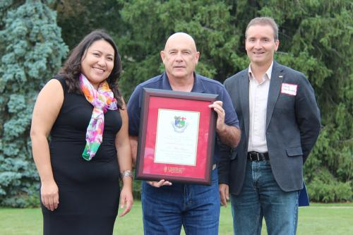 Rocio Morales Rayas, Al Lauzon and Rene Van Acker pose outside with framed award