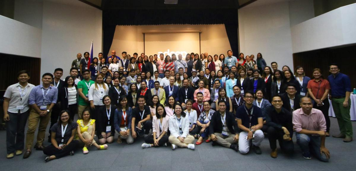 Group photo of ADCEP conference participants standing and sitting