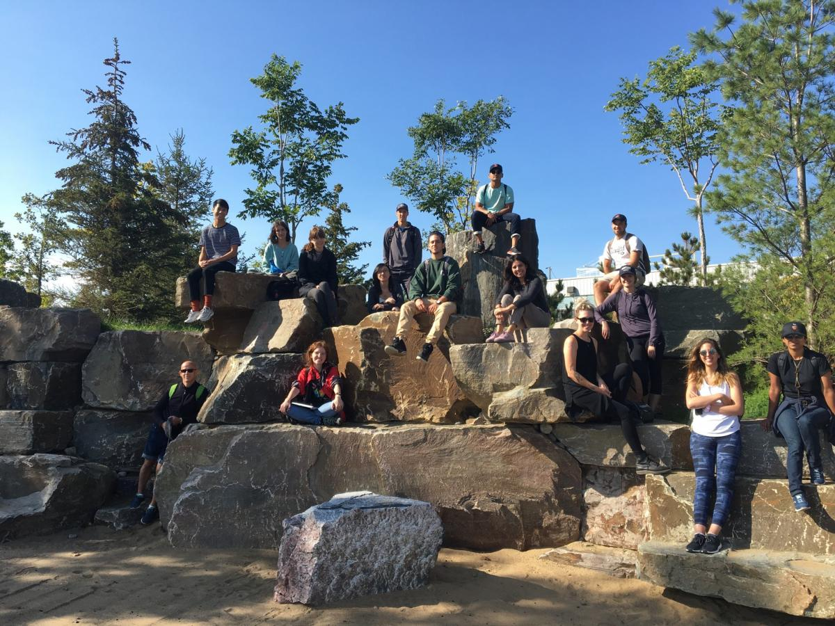 Students standing and sitting on rocks