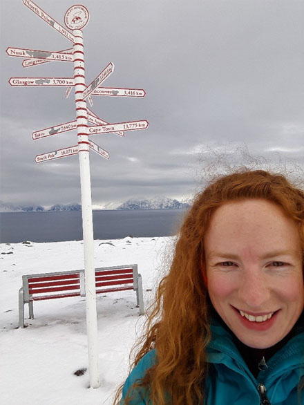Hilary Sadowsky in front of sign post at Pond Inlet