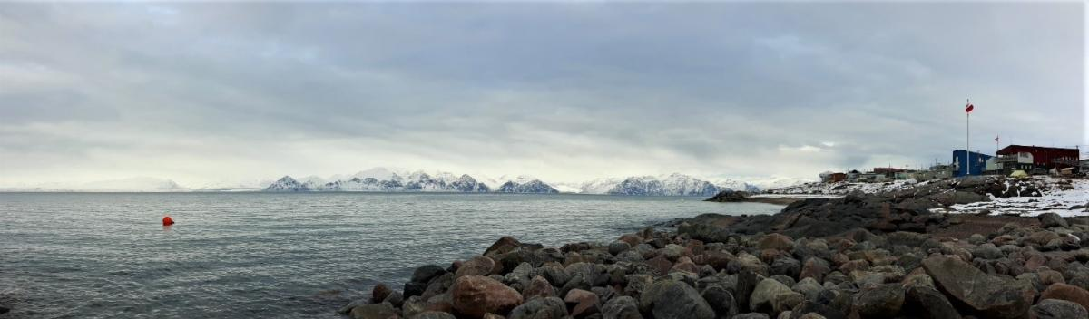View of water and rocks facing mountains of Bylot Island