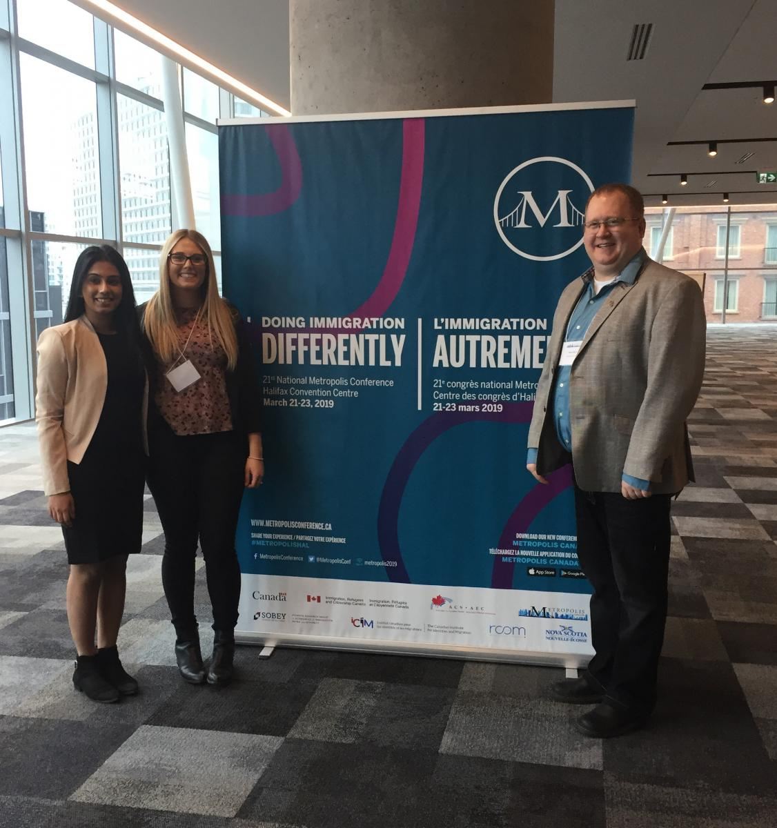 Three people in front of 2019 Metropolis Immigration Conference Banner