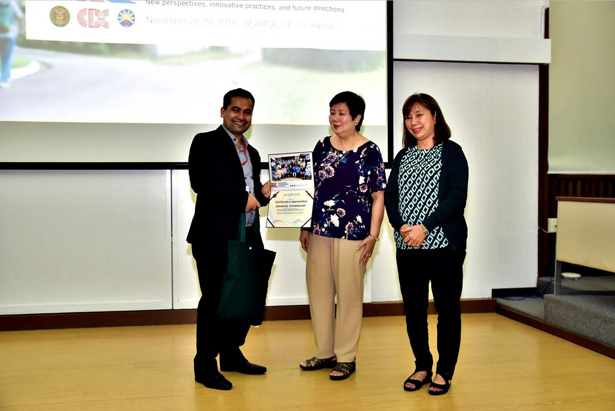 Dr. Chowdhury receiving certificate from two individuals