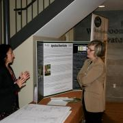Pam Duesling (left) sharing information on her research with participant at table booth