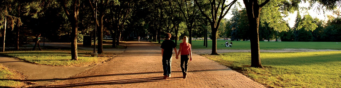 Two students holding hands walking down Alumni Walk