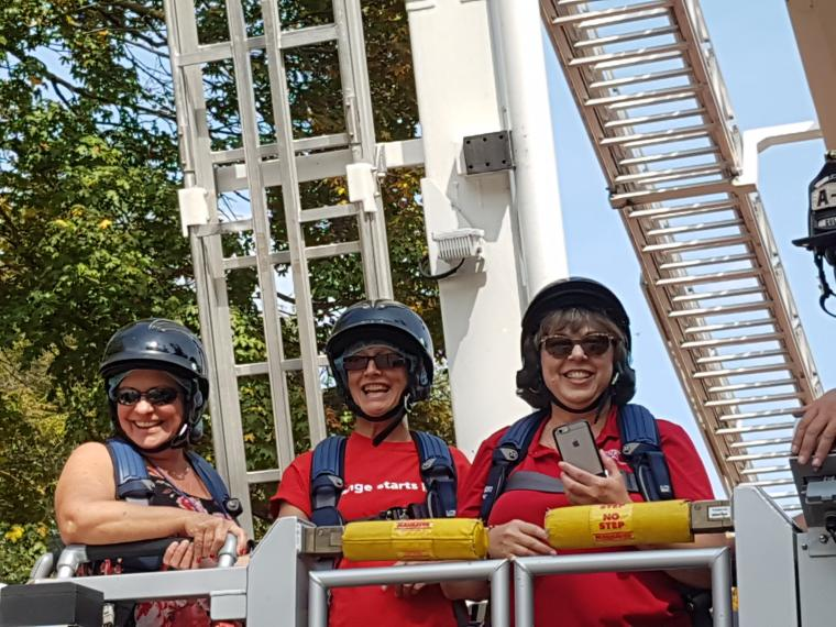 United Way supporters ride up in the bucket for an aerial view of campus.