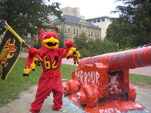 Gryphon mascot in front of campus cannon Old Jeremiah