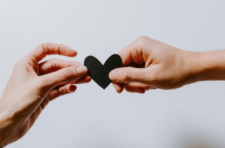Photo of two hands holding a heart.